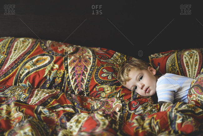 Little boy resting on red paisley pattern bedding