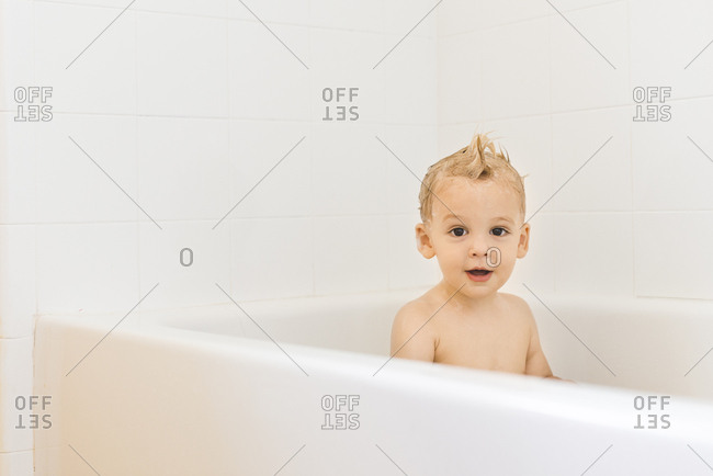 Little boy with silly hairstyle in the bathtub