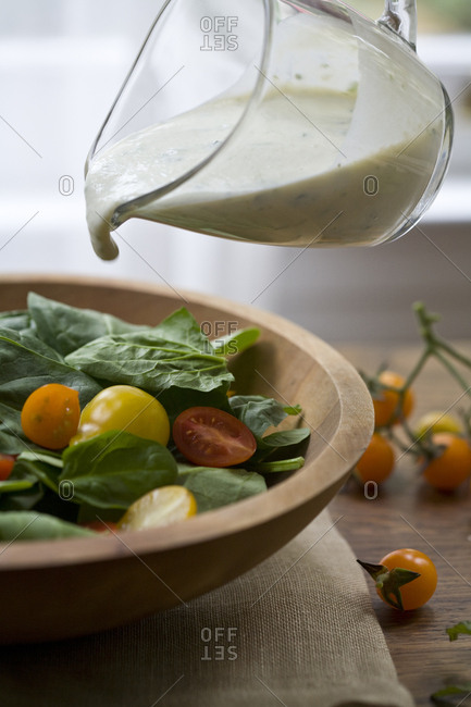 Creamy dressing poured on a spinach salad
