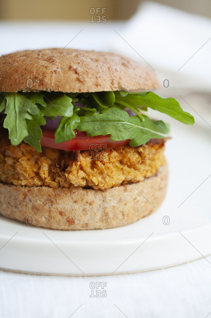 vegetarian burger on whole wheat bun with arugula, tomato
