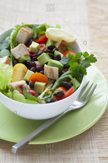 Salad with chicken, avocado, olives, tomatoes, lemon and butter lettuce