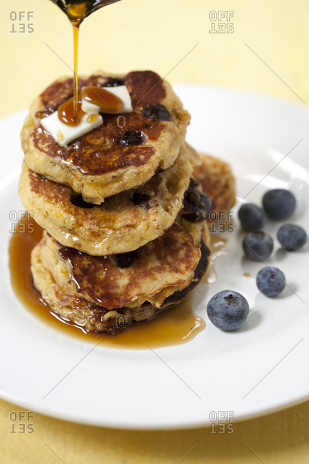 Blueberry pancakes on plate with butter and syrup