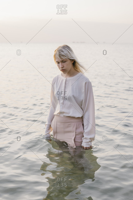 Smiling young woman standing in clothes in sea water in Vietnam