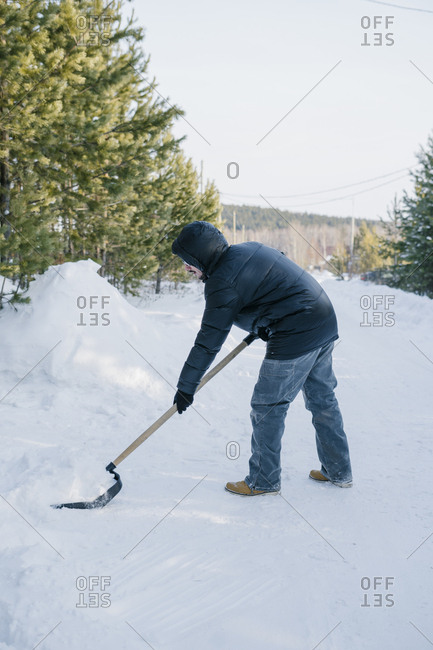 Young man cleans the snow next to the car outside the city