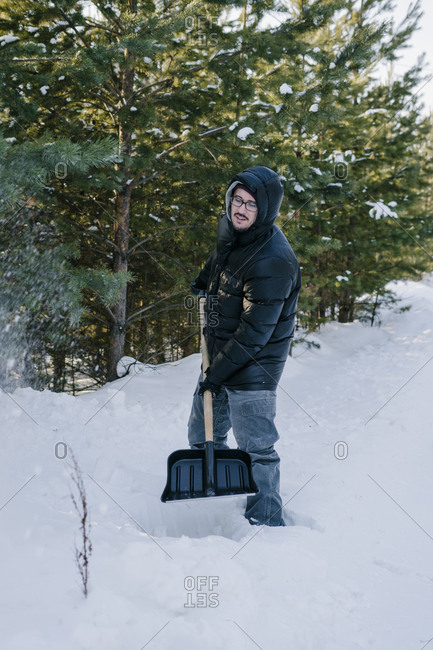 Man with a shovel in hand cleans snow near the house