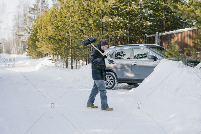 A man with a shovel in his hands cleans the snow near the parking lot