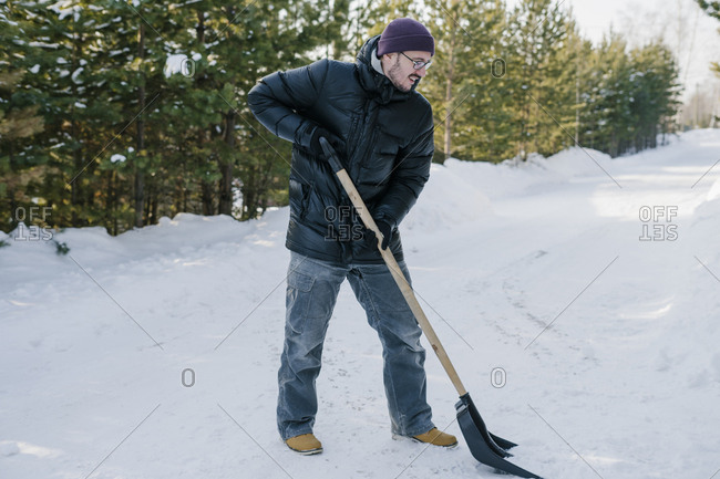 A man with a shovel in his hands cleans the snow near the road