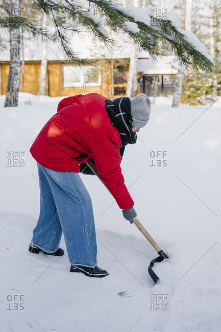 A woman with a shovel cleans snow from the path outside the house