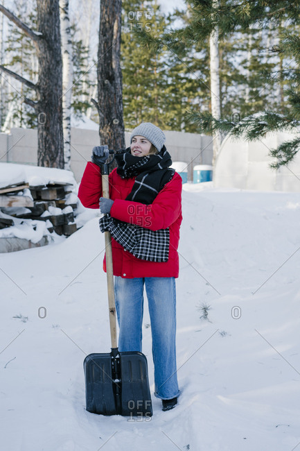 A woman in a red jacket with a shovel cleans a path from the snow