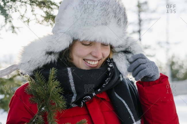 Portrait of a beautiful woman in a fur hat in winter with a smile near the Christmas tree