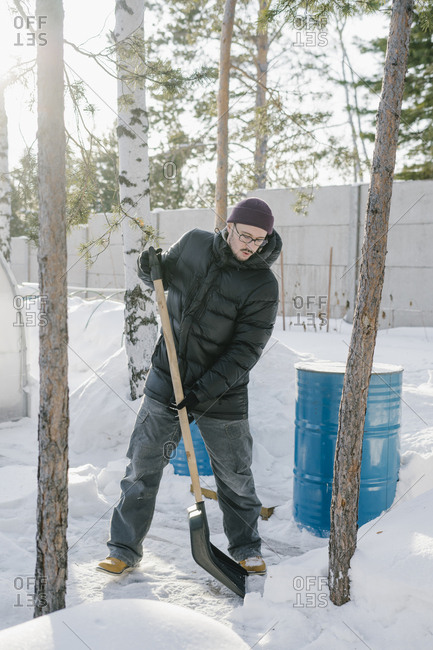 Young man cleans the snow in the area against the sunset
