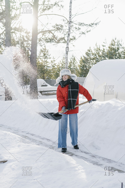 A woman in a winter hat shovels snow from a path in a village