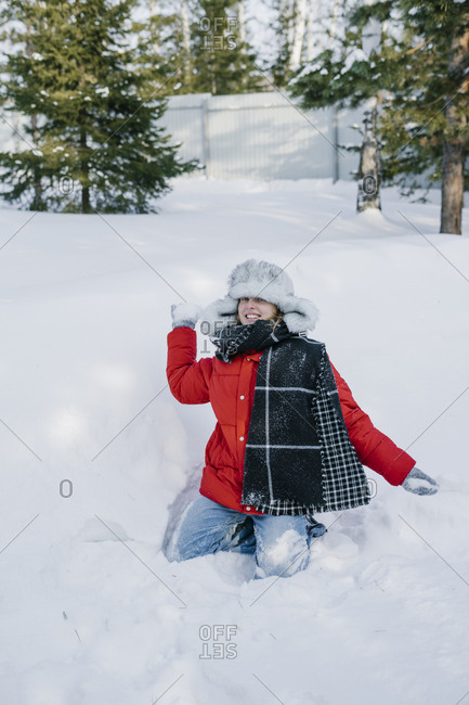 Portrait of beautiful young woman in winter hat sitting on the snow and throwing snowballs