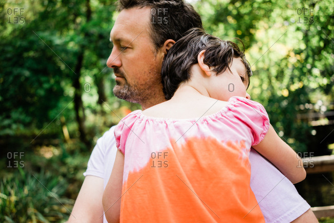 Father carrying daughter through green park