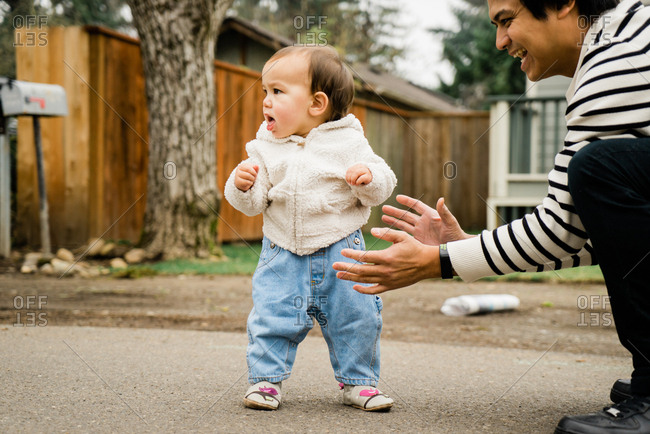 Father helping baby son learn to walk