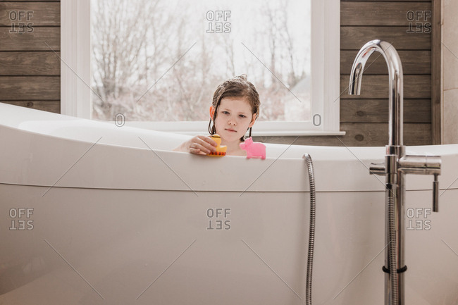 Girl plays with toys during her bath