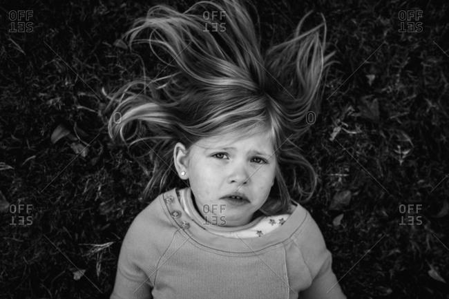 Sad girl laying in grass