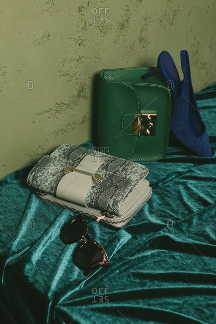 Purses, heel and sunglasses set on a green velvet bakground