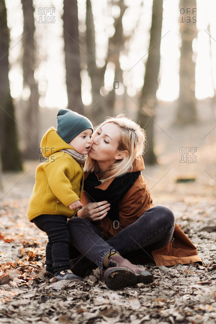 Mother kissing baby while sitting in the forest