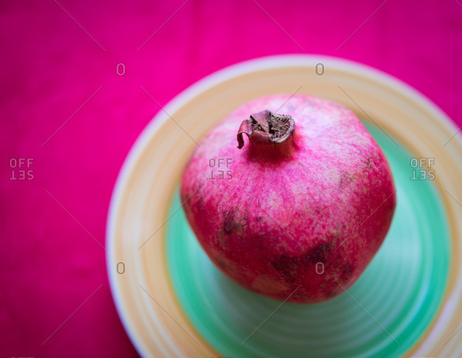 pomegranate in a dish set on a violet table.