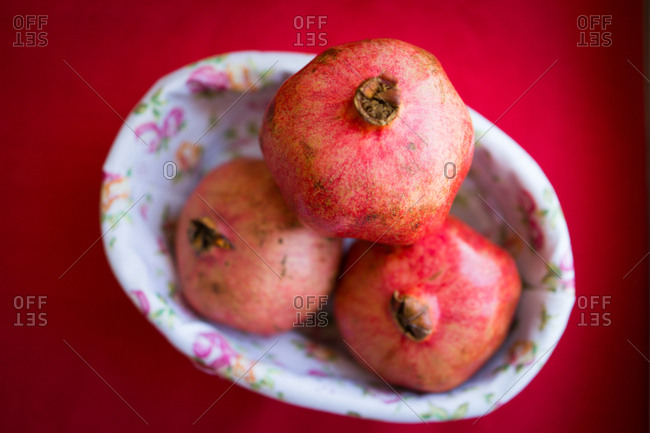pomegranates in a floral dish set on a red table.