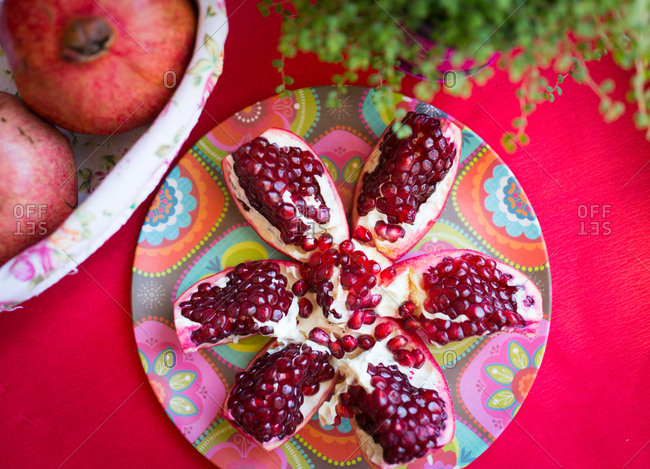 pomegranate split open set on a floral plate on a red table..
