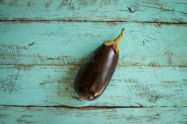 Solo eggplant on a turquoise wooden table.