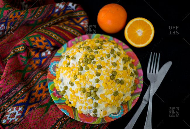 Potato salad with corn in a bowl on a blanket with an orange and silverware set on a black background.