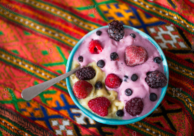 smoothie in blue bowl with a spoon in it set on a Mexican style blanket.