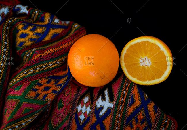 An orange cut in half on a blanket set on a black background