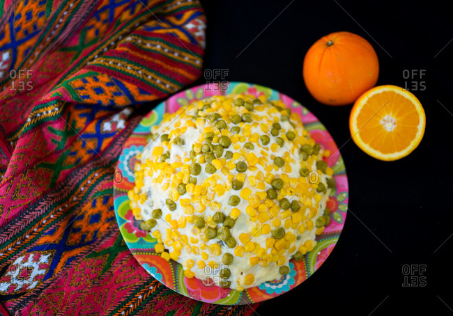 Potato salad with corn in a bowl, with an orange on a blanket set on a black background.