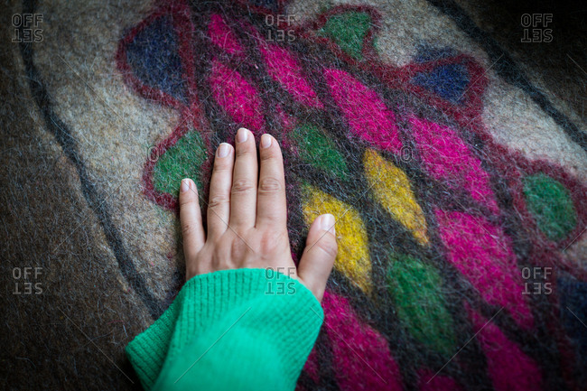 touching Iranian carpet made by wool
