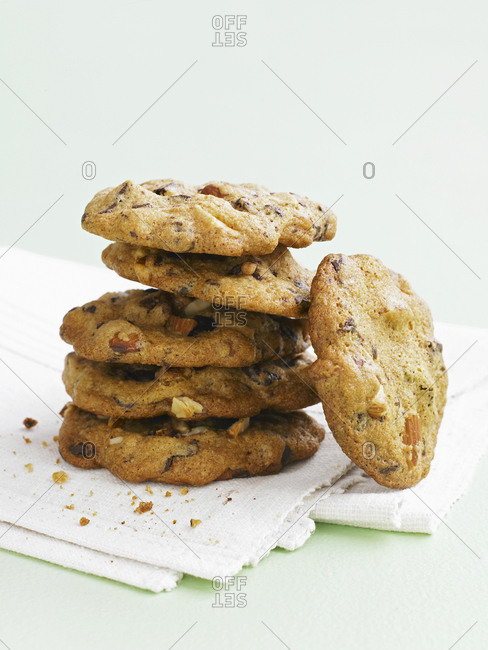 A stack of chocolate and mixed nuts cookies on a white napkin and white background.