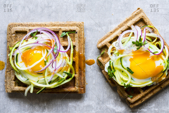 Savory whole grain waffles topped with zucchini zoodles, egg and red onion