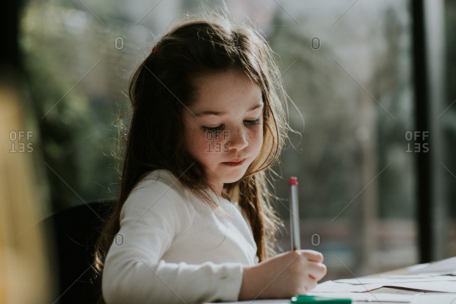 Cute young girl writing on paper