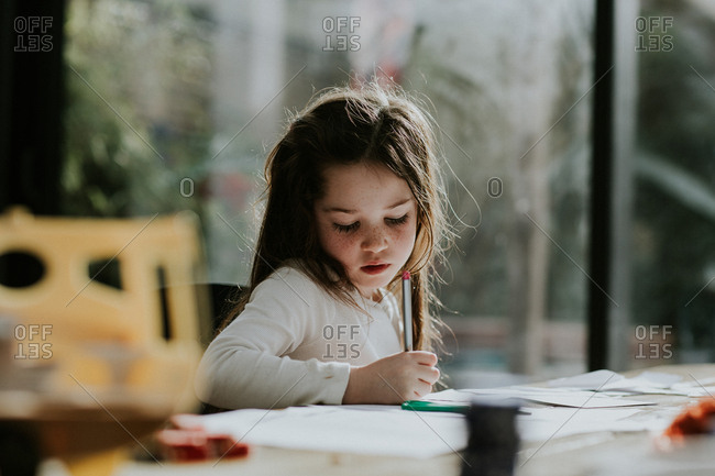 Young girl drawing with a pen at the table