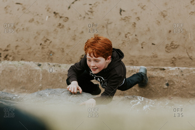 Boy climbing on a store wall at the beach