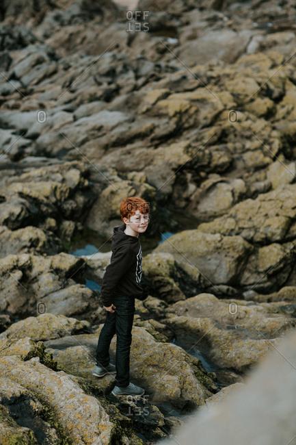 Boy walking along rocky landscape