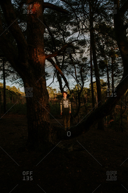 Boy standing in dramatic light at sunset