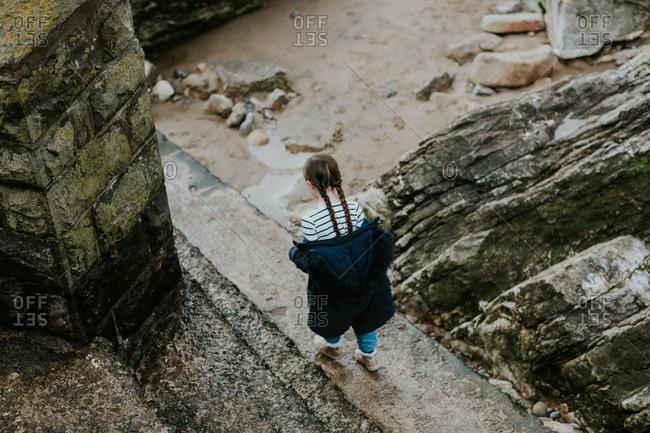 Young girl walking on stone ledge