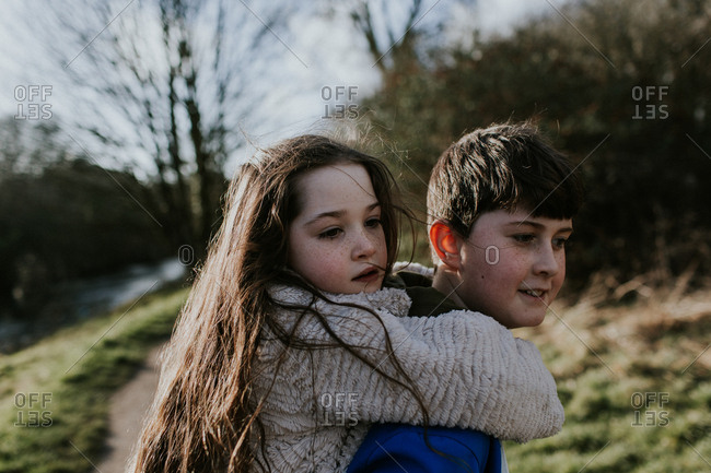 Brother giving his sister a piggy back ride in nature