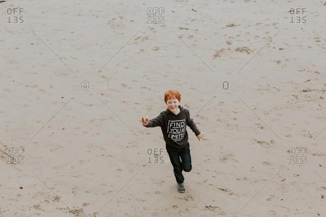 Young boy running on a sandy beach
