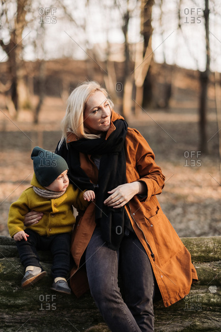 Mother sitting on log in the forest with baby at sunset