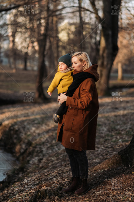 Mother holding baby during a walk in the forest