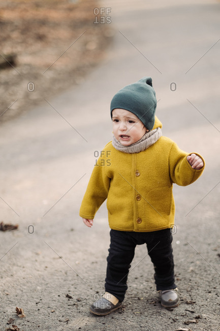 Baby wearing yellow jacket and green knit hat on a nature trail