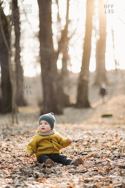 Baby wearing yellow jacket and green knit hat sitting in leaves on the ground in the woods