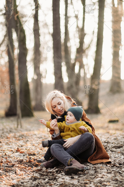 Mother sitting on the ground in the forest with baby at sunset
