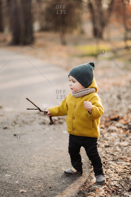 Baby wearing yellow jacket and green knit hat walking with a stick on a nature trail