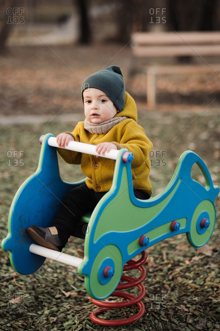Baby playing on bouncy car toy at a park