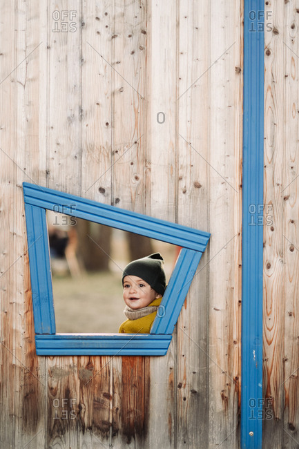 Baby looking through window in a tree house at a park